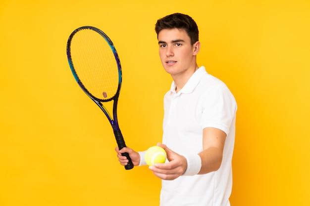 Homem de jogador de tênis adolescente bonito isolado no fundo amarelo jogando tênis