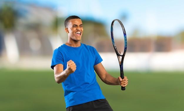 Homem de jogador de tênis americano africano ao ar livre