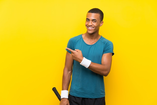 Homem de jogador de tênis americano africano apontando para o lado para apresentar um produto