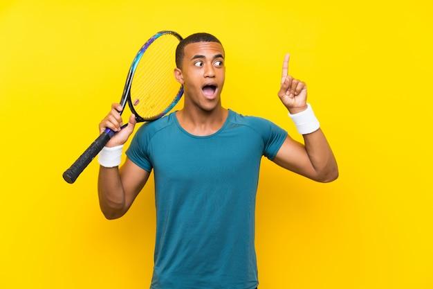 Homem de jogador de tênis americano africano, com a intenção de perceber a solução, levantando um dedo