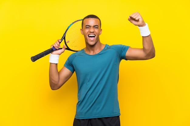 Homem de jogador de tênis americano africano comemorando uma vitória