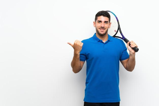Homem de jogador de tênis jovem bonito na parede branca, apontando para o lado para apresentar um produto