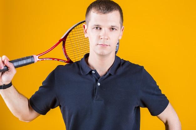 Homem de jogador de tênis profissional em uma parede amarela brilhante