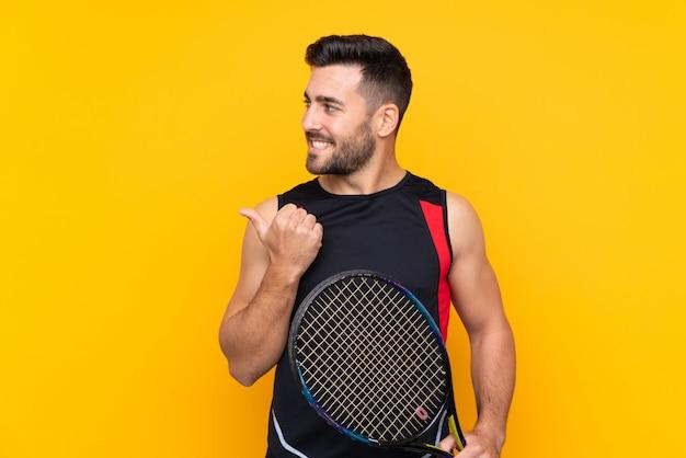 Homem de jogador de tênis sobre parede amarela isolada, apontando para o lado para apresentar um produto