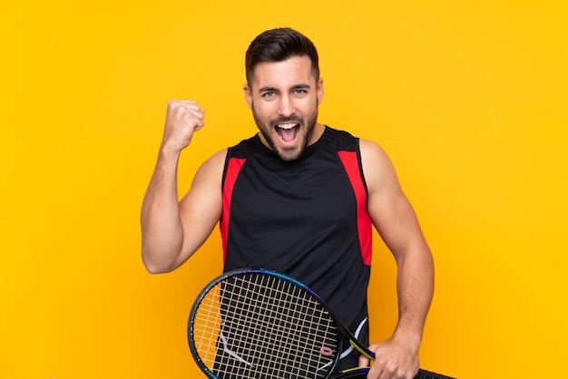 Homem de jogador de tênis sobre parede amarela isolada comemorando uma vitória
