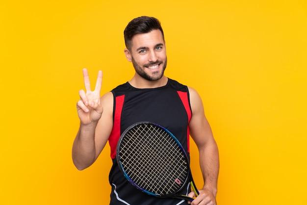 Homem de jogador de tênis sobre parede amarela isolada, sorrindo e mostrando sinal de vitória