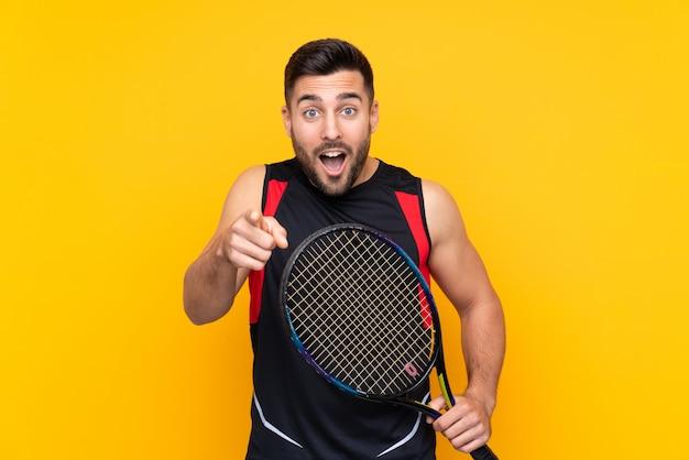 Homem de jogador de tênis sobre parede amarela isolada surpreso e apontando a frente