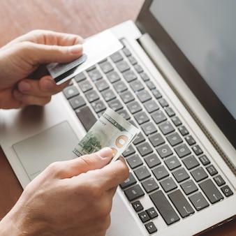 Homem de jogos de azar online com cartão de crédito e dinheiro pronto para jogar no cassino da internet em seu laptop