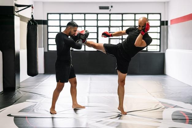 Homem de kickboxing treinando com seu treinador com luvas de boxe vermelhas chutando diretamente nas mãos do treinador em uma academia
