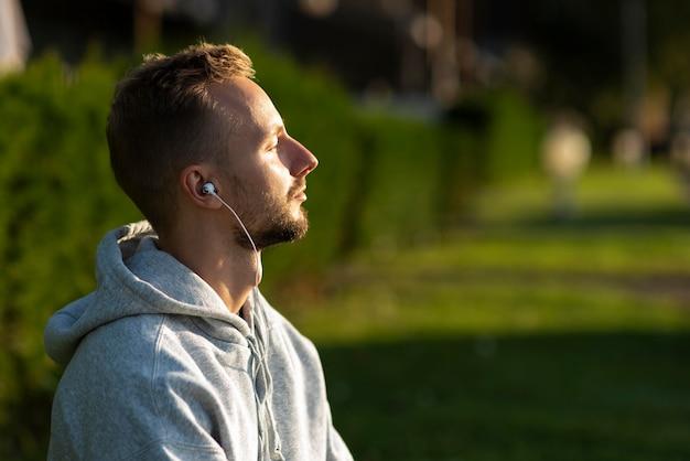 Homem de lado ouvindo música enquanto medita