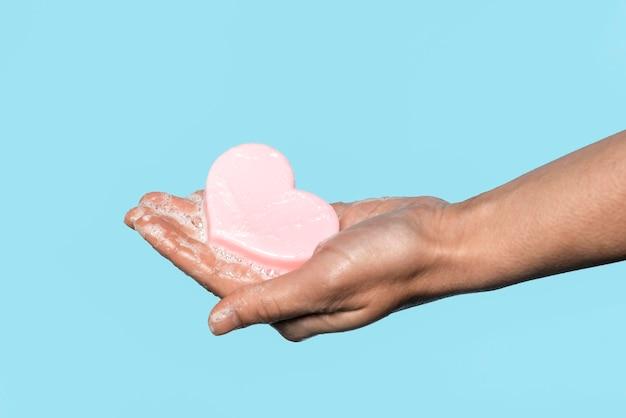 Homem de lado segurando um sabonete em forma de coração