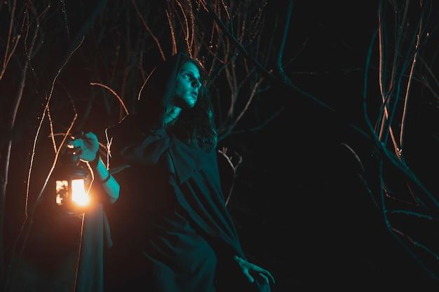 Homem de lado segurando uma lanterna no meio da noite