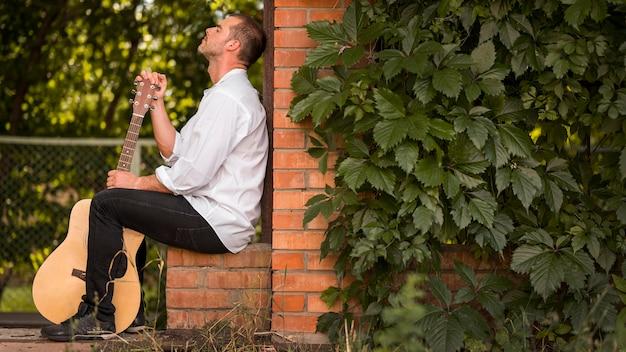 Homem de lado sentado com seu violão ao ar livre