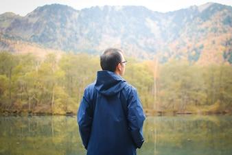 Homem de liberdade ficar do lado do lago contra floresta de outono natural e montanhas