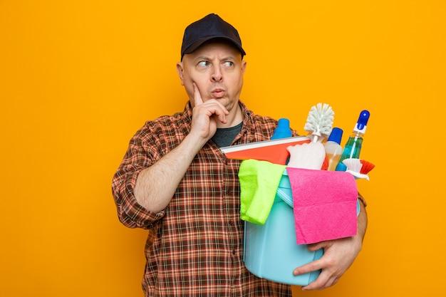 Homem de limpeza com camisa xadrez e boné segurando um balde com ferramentas de limpeza, olhando para o lado com o rosto carrancudo e perplexo em pé sobre um fundo laranja