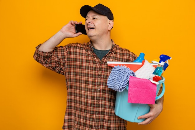 Homem de limpeza com camisa xadrez e boné segurando um balde com ferramentas de limpeza sorrindo alegremente enquanto fala no celular