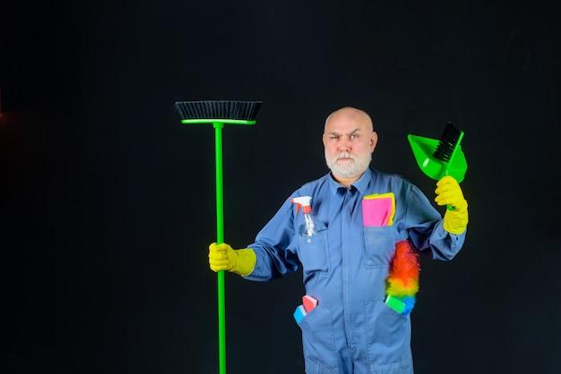 Homem de limpeza com ferramentas de limpeza homem barbudo de uniforme com vassoura e colher de limpeza doméstica