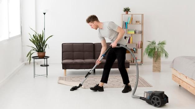 Homem de limpeza com vácuo