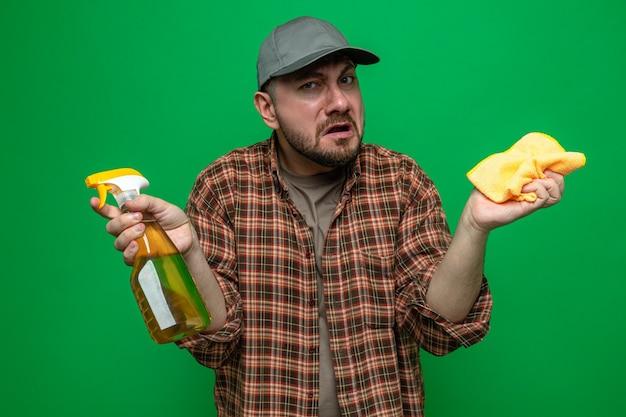 Homem de limpeza eslavo sem noção segurando panos de limpeza e limpador em spray