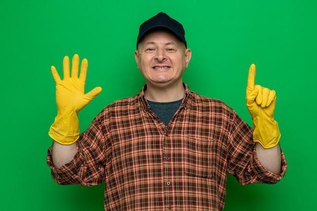 Homem de limpeza feliz e positivo com camisa xadrez e boné, luvas de borracha, sorrindo, mostrando o número seis com os dedos