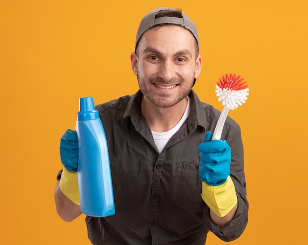 Homem de limpeza jovem feliz vestindo roupas casuais e boné em luvas de borracha segurando uma escova de limpeza e garrafa com material de limpeza sorrindo alegremente em pé sobre a parede laranja