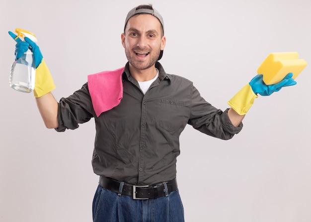 Homem de limpeza jovem vestindo roupas casuais e boné em luvas de borracha segurando um spray de limpeza e uma esponja com um pano no ombro, parecendo feliz e animado em pé sobre a parede laranja