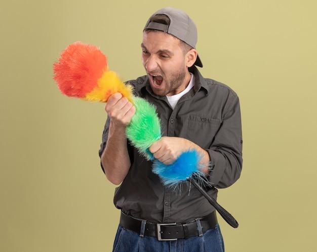 Homem de limpeza jovem zangado, vestindo roupas casuais e boné, segurando um espanador colorido, gritando com uma expressão agressiva em pé sobre a parede verde
