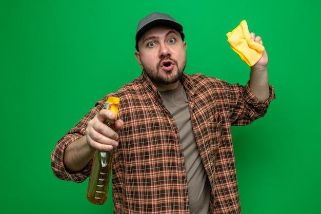 Homem de limpeza surpreso segurando panos de limpeza e limpador em spray