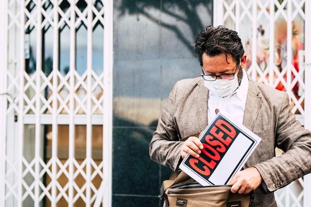 Homem de loja fracassado com placa de venda fora de sua loja e máscara de proteção contra vírus