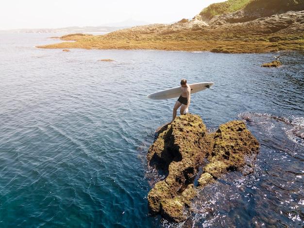Homem de longo alcance se preparando para surfar