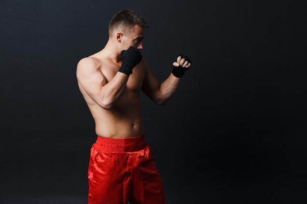 Homem de luta livre em pé no fundo preto com bandagens de boxe