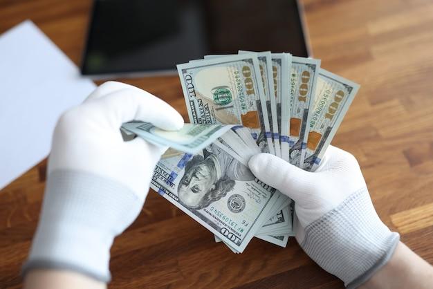 Homem de luvas brancas, contando closeup de dólares americanos. conceito de verificação de autenticidade de dinheiro