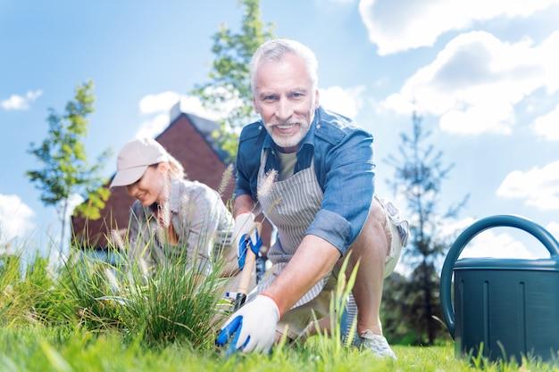 Homem de luvas. homem maduro, barbudo, de olhos escuros e luvas brancas, sentindo-se feliz enquanto trabalhava perto do canteiro do jardim