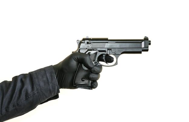 Homem de luvas pretas está segurando uma arma. assassino criminoso.