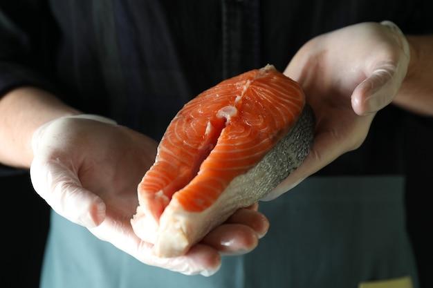 Homem de luvas segurando carne de salmão no escuro
