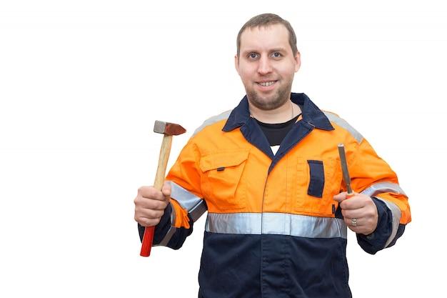 Homem de macacão com um martelo e formão