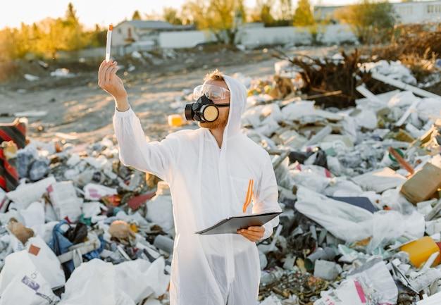 Homem de macacão na pílula do lixo. fazendo pesquisas. conceito de ecologia, poluição ambiental.