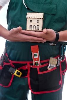 Homem de macacão segurando a chave e o modelo da casa de madeira