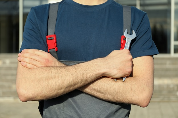 Homem de macacão segurando uma chave com os braços cruzados. inspeção automóvel