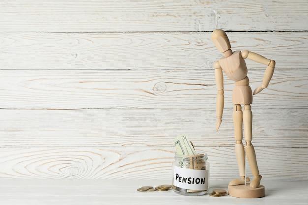 Homem de madeira e jarra com dinheiro na superfície de madeira