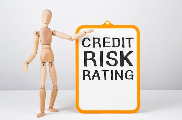 Homem de madeira mostra com uma mão no quadro branco com classificação de risco de crédito de texto.