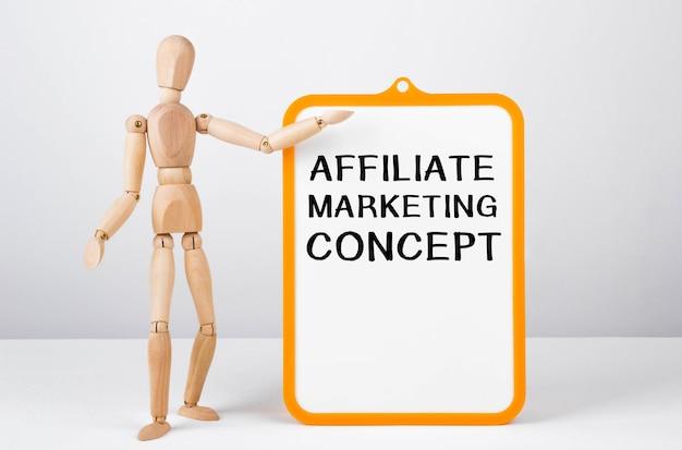Homem de madeira mostra com uma mão no quadro branco com o texto conceito de marketing afiliado.