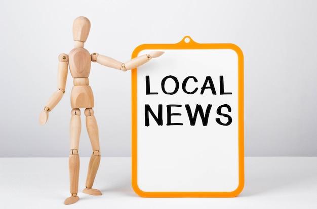 Homem de madeira mostra com uma mão no quadro branco com o texto local news.