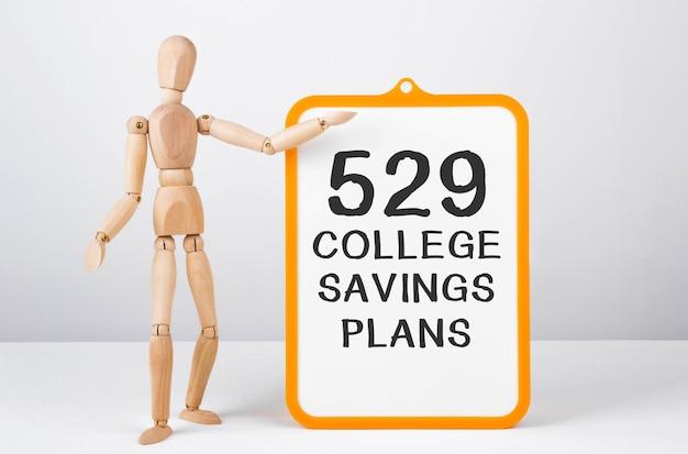 Homem de madeira mostra com uma mão no quadro branco com planos de poupança de faculdade de texto 529.