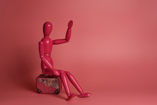 Homem de madeira rosa senta-se em uma mala contra um fundo rosa