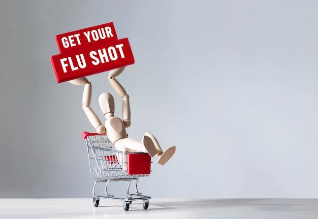 Homem de madeira segura um bloco de madeira vermelho com a palavra tome sua vacina contra a gripe, conceito