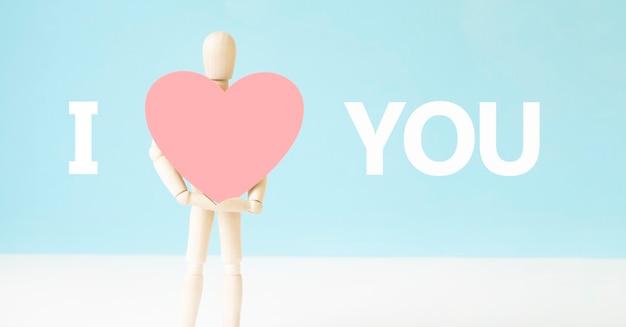 Homem de madeira segurando coração sobre fundo azul. texto eu te amo. sinal de símbolo de ideia, conceito de amor