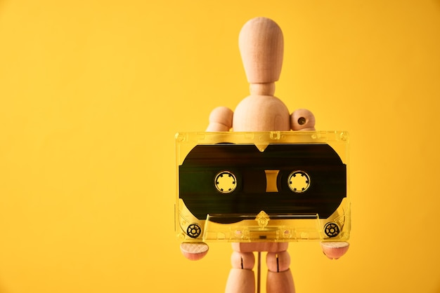 Homem de madeira segurando fita cassete retrô em amarelo