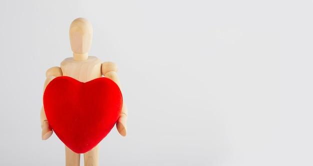 Homem de madeira segurando uma estatueta de coração nas mãos em um branco