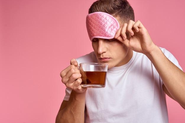 Homem de manhã com uma xícara de chá e uma máscara para dormir